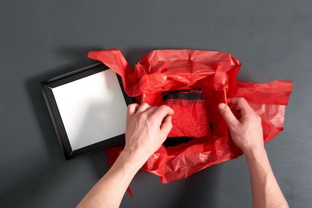 Man verpakking geschenkdoos met stijlvolle sexy rode ondergoed op grijze houten tafel. close-up bekijken.