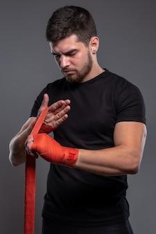 Man verpakt hads met rode professionele bokstape