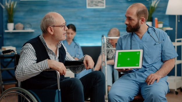 Man verpleegster en oude patiënt kijken naar groen scherm op tablet