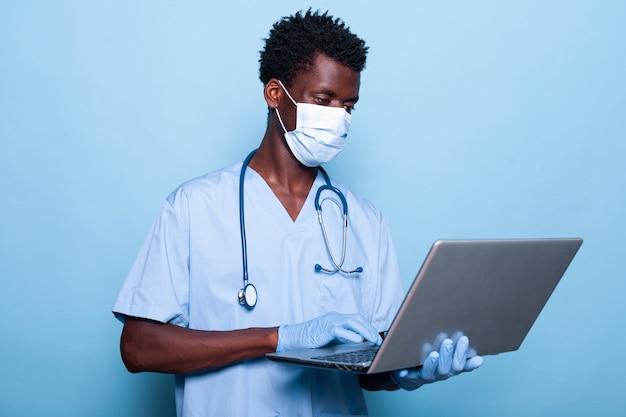 Man verpleegster met uniform bedrijf laptop over geïsoleerde achtergrond
