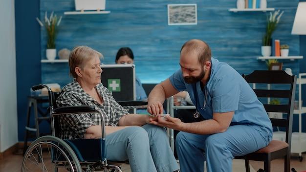 Man verpleegster zetten oximeter bij de hand van oudere gehandicapte vrouw