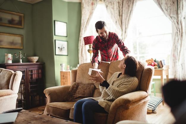Man verrassende vrouw met een geschenk in de woonkamer