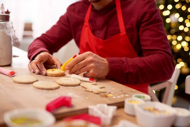 Man versieren koekjes in de keuken