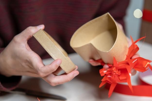Man versiert een hartvormige geschenkdoos met rode linten