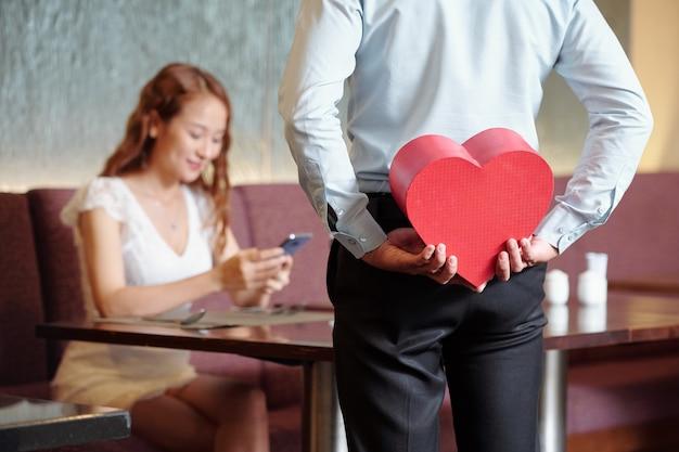 Man verstopt cadeau in hartvormige doos voor vriendin die aan cafétafel zit en sms-berichten op smartphone controleert