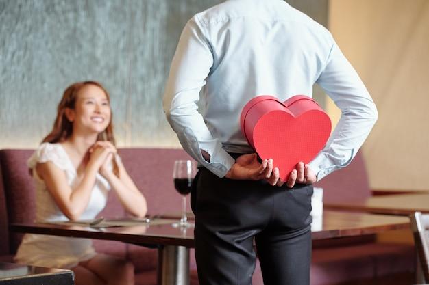Man verstopt romantisch cadeau voor vriendin achter zijn rug als hij aan tafel in restaurant staat