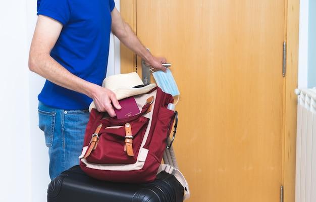 Man vertrekt naar huis voor vakantie met koffer en paspoort en masker. ruimte kopiëren.