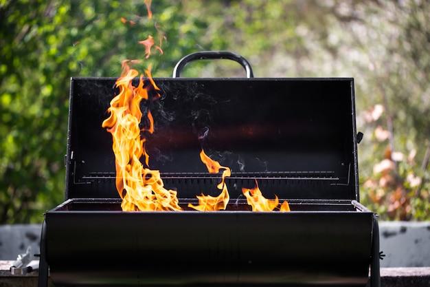 Man verwarmt de bbq-grill en bereidt zich voor op het grillen van sommige soorten vlees