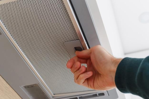 Man verwijdert een filter uit afzuigkap voor reiniging of onderhoud