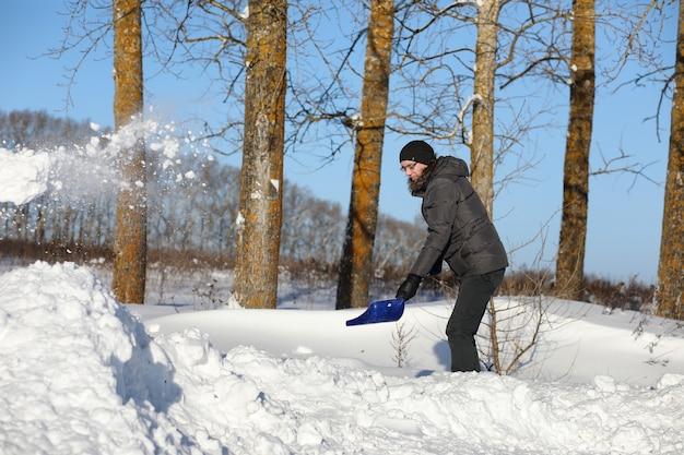 Man verwijdert sneeuw met schop van de weg in de winterdag