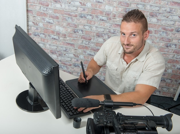 Man video-editor met grafisch tablet en professionele videocamera