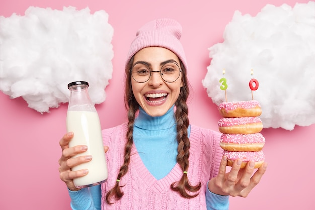 Man viert haar verjaardag houdt heerlijke donuts met brandende kaarsen en glazen fles melk glimlacht breed draagt casual kleding geïsoleerd op roze