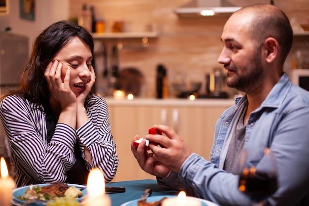 Man viert relatie en vraagt vriendin om met hem te trouwen tijdens het avondeten. man vraagt zijn vriendin ten huwelijk in de keuken tijdens een romantisch diner. gelukkige blanke vrouw die lacht wordt gesproken