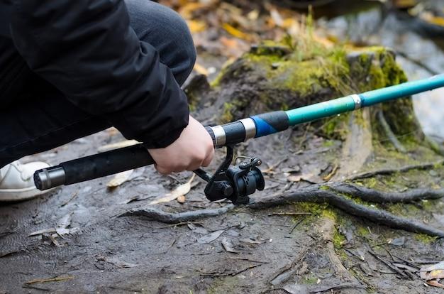 Man vissen in een wild meer. mannelijke handen houden een hengel, close-up. herfstvissen bij koud weer.