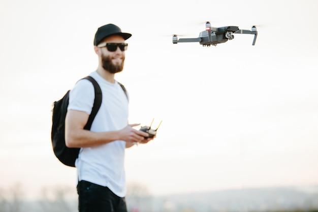 Man vliegt een drone in de stad met behulp van een controller Premium Foto