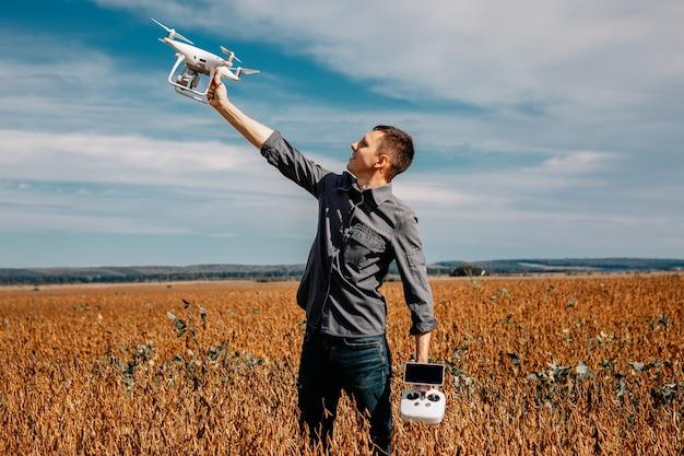 Man vliegt een drone in het gele veld
