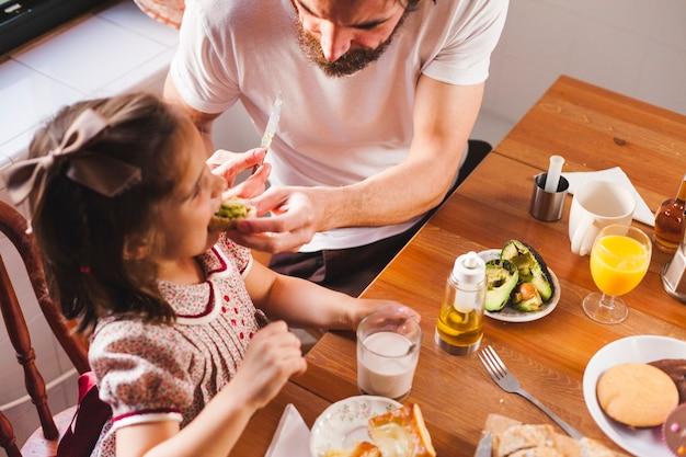 Man voederen meisje bij het ontbijt
