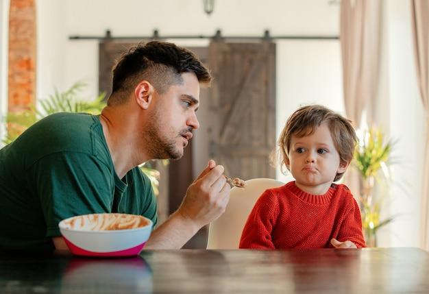 Man voedt een kind aan een tafel in de eetkamer