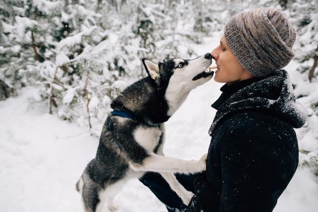 Man voedt zijn husky hondenkoekjes van mond tot mond buiten in besneeuwd winterweer