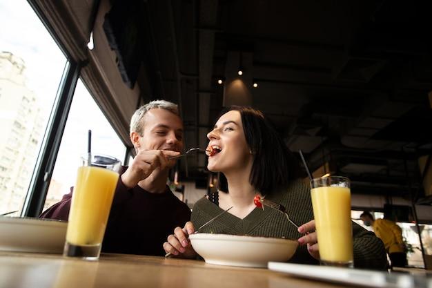 Man voedt zijn vriendin een tomaat