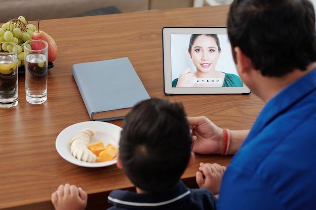 Man voedt zoon met fruit als ze moeder videobellen via tafelcomputer