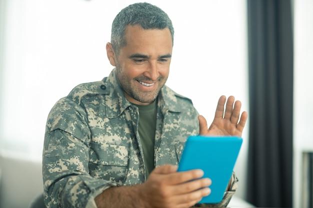 Man voelt zich gelukkig. militaire man in uniform voelt zich gelukkig terwijl hij zijn familie op het scherm ziet