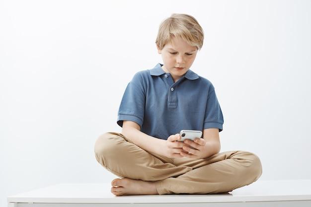 Man voelt zich intens bij het spelen van favoriete game op de smartphone. ernstige mooie kleine jongen met blond haar zittend op de vloer met gekruiste voeten, telefoon vast te houden en naar het scherm van het apparaat te staren