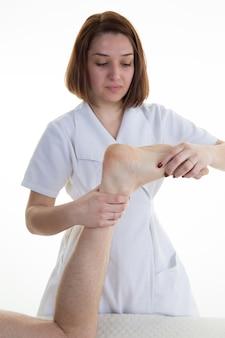 Man voetreflexologie ontvangen door vrouwelijke therapeut glimlachen