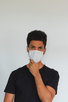 Man volwassen zwarte dragen coronavirus masker denken geïsoleerd op wit