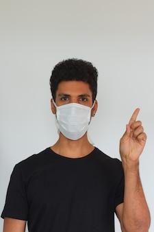 Man volwassen zwarte dragen coronavirus masker wijzen geïsoleerd op een witte achtergrond