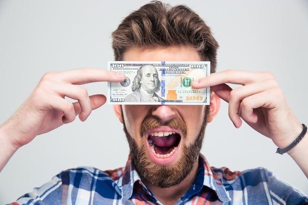 Man voor zijn ogen met een biljet van de amerikaanse dollar