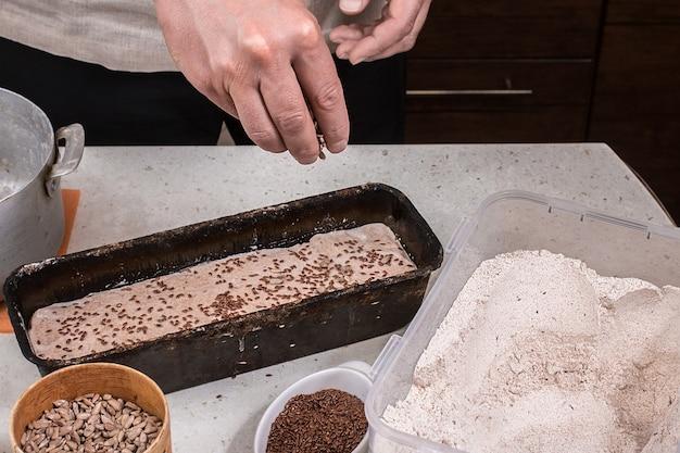 Man voorbereiding van brooddeeg op houten tafel