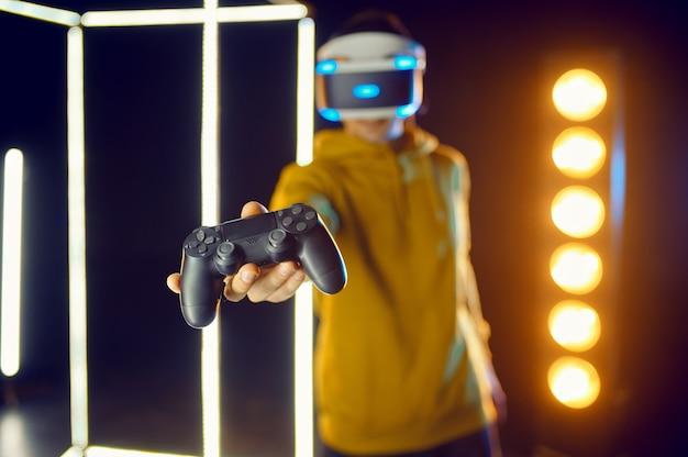 Man vrije tijd met behulp van virtual reality headset en gamepad in lichtgevende kubus, vooraanzicht