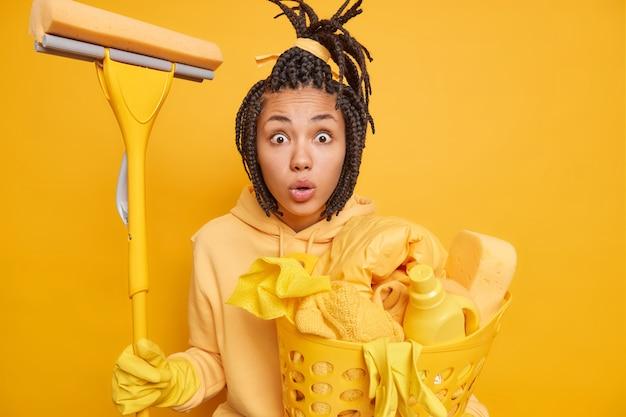 Man vrouw doet de was en wast alles thuis houdt dweil vast om schoon te maken draagt hoodie en beschermende rubberen handschoenen aan handen