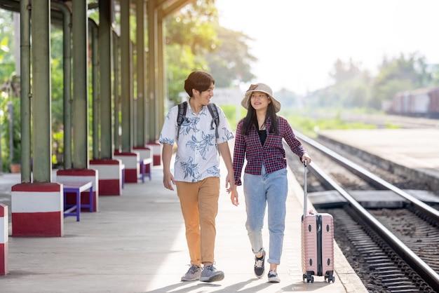 Man & vrouw met rugzak wachten op trein op treinstation. liefdevol stel reiziger reist samen op vakantie