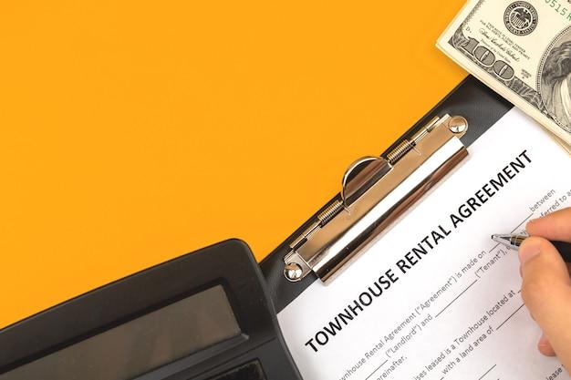 Man vullen herenhuis huurovereenkomst contract formulier. bureau met rekenmachine en geld. bovenaanzicht foto