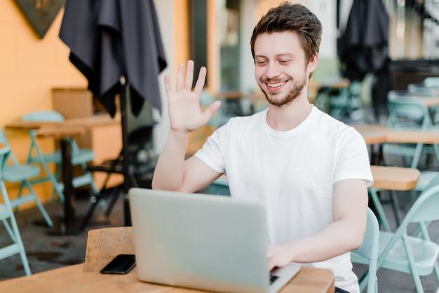 Man waait hallo tegen laptop webcam
