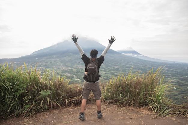 Man wandelaar met een rugzak bovenop de bergrug, het concept van motivatie en doelverwezenlijking