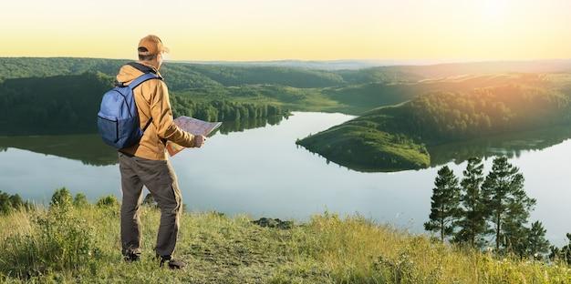 Man wandelaar met rugzak controleert kaart om een routebeschrijving in wildernisgebied te vinden. banier.