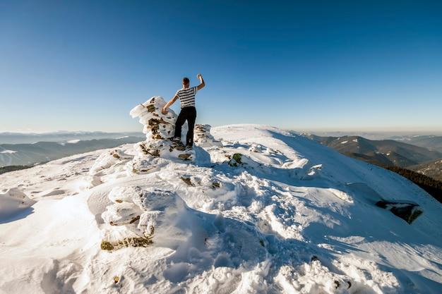 Man wandelaar op de top van een berg in de winter