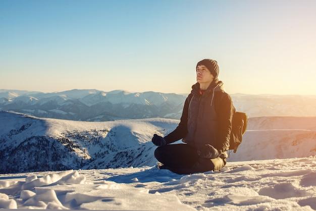 Man wandelaars toeristen zitten mediteren na een harde beklimming alleen