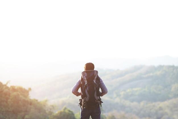 Man wandelen bij zonsondergang bergen met zware rugzak travel lifestyle reislust avontuur concept zomervakanties buiten alleen in het wild