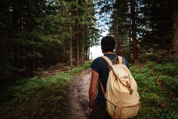 Man wandelen in de bergen met zware rugzak