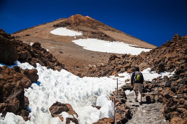 Man wandelen op vulkaan teide in tenerife, canarische eilanden, spanje