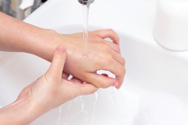 Man wast zijn handen. dient schuim van antibacteriële zeep in. bescherming tegen bacteriën, coronavirussen. hand hygiëne. handen wassen met water. veel handen