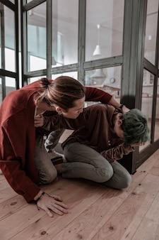 Man wegduwen. hulpeloze vrouw met groen haar die haar man van zich af duwt terwijl ze aan geweld lijdt