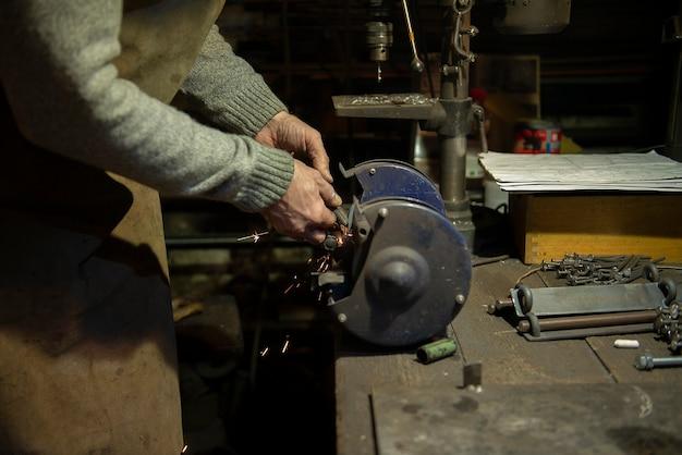 Man werk in huis workshop garage met haakse slijper, schuren van metaal maakt vonken close-up, diy en ambachtelijke concept