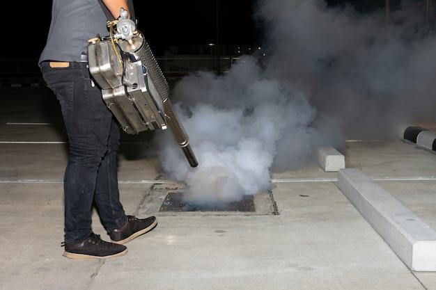 Man werknemer benevelt insecticide om muggen te elimineren om verspreiding van knokkelkoorts en zika-virus te voorkomen