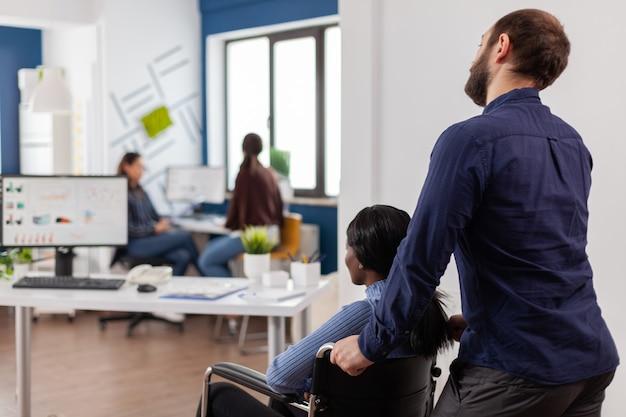 Man werknemer helpt zijn ongeldige afrikaanse collega die op de werkplek komt en rolstoel bij het bureau duwt