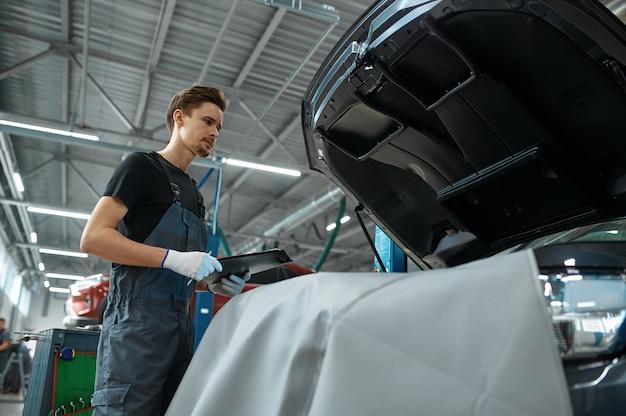 Man werknemer met checklist staat op de motorkap in mechanische werkplaats
